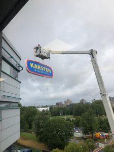 Reclamebord wordt opgehangen op het kantoorpand van Karsten International